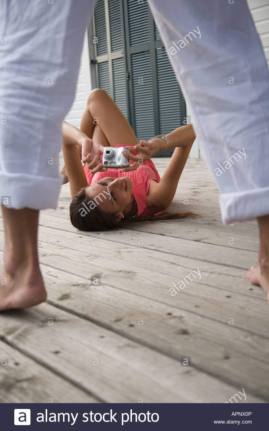 Woman laying on porch taking photo of man - Stock Image