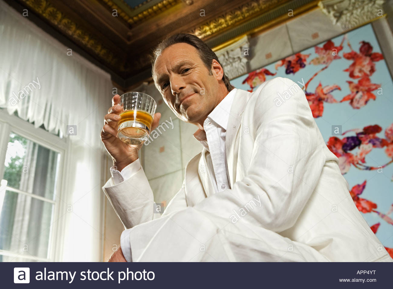 Low angle view of a mature man holding a glass of whiskey Stock Photo
