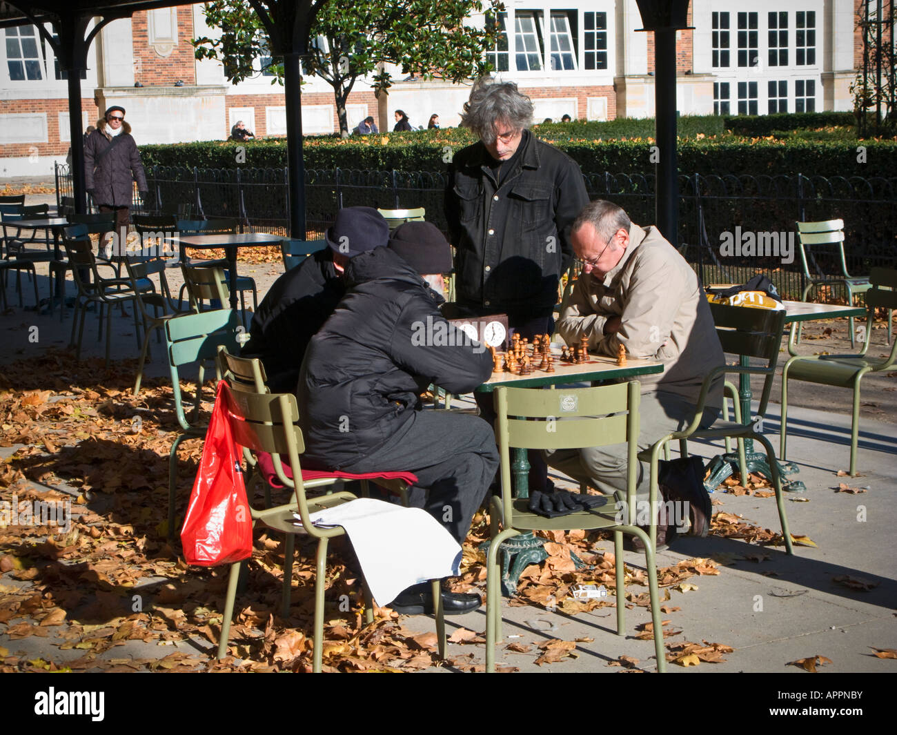 Four men playing chess in the late autumn sun in the Jardin du Luxembourg city park in Paris France Europe Stock Photo