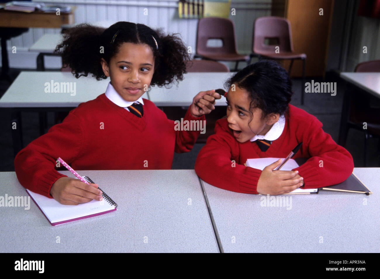Two little black girls in a classroom.  One is pulling the others hair. - Stock Image
