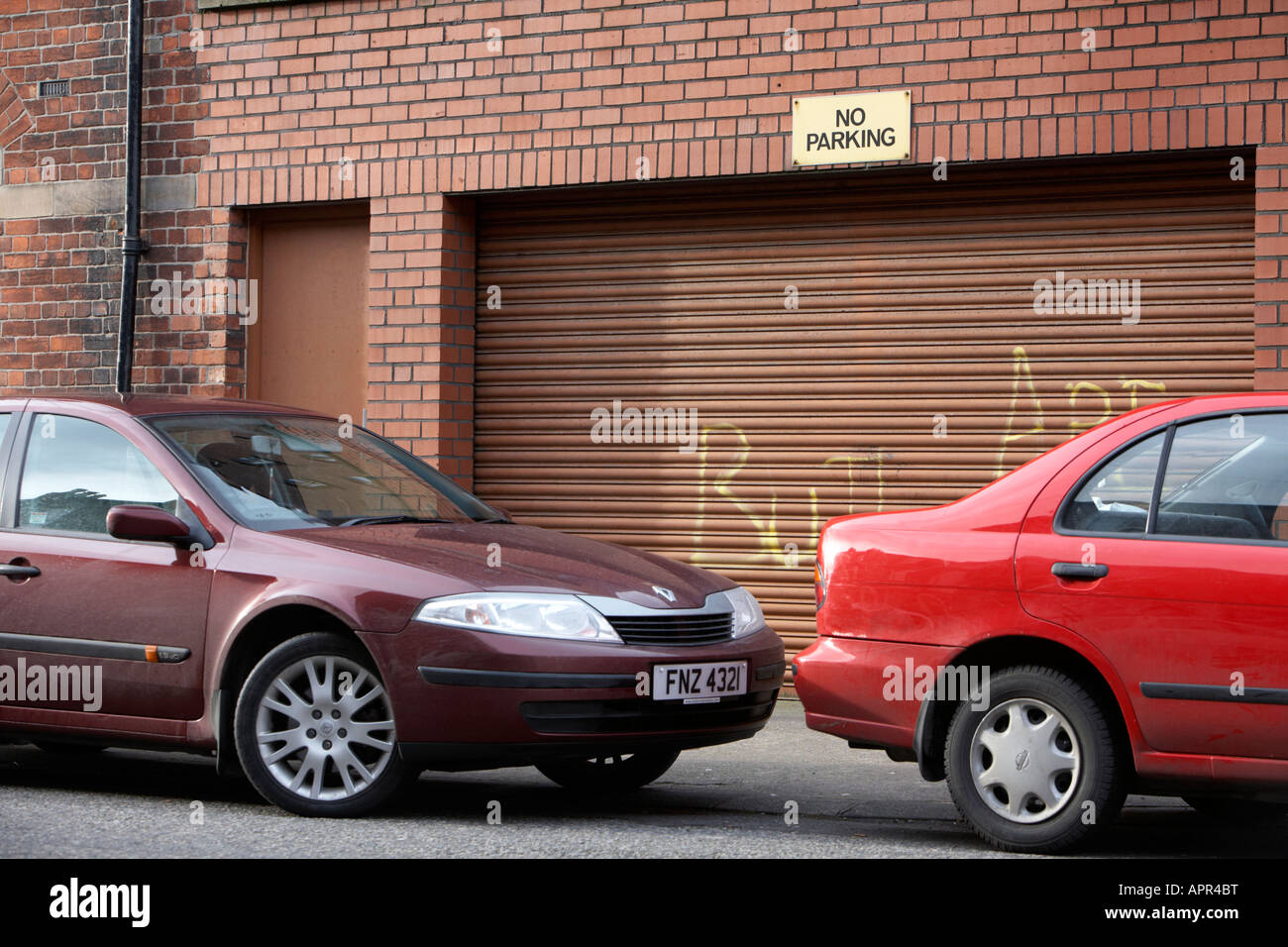 two cars parked in front of steel garage shutter with no parking sign Belfast Northern Ireland UK - Stock Image