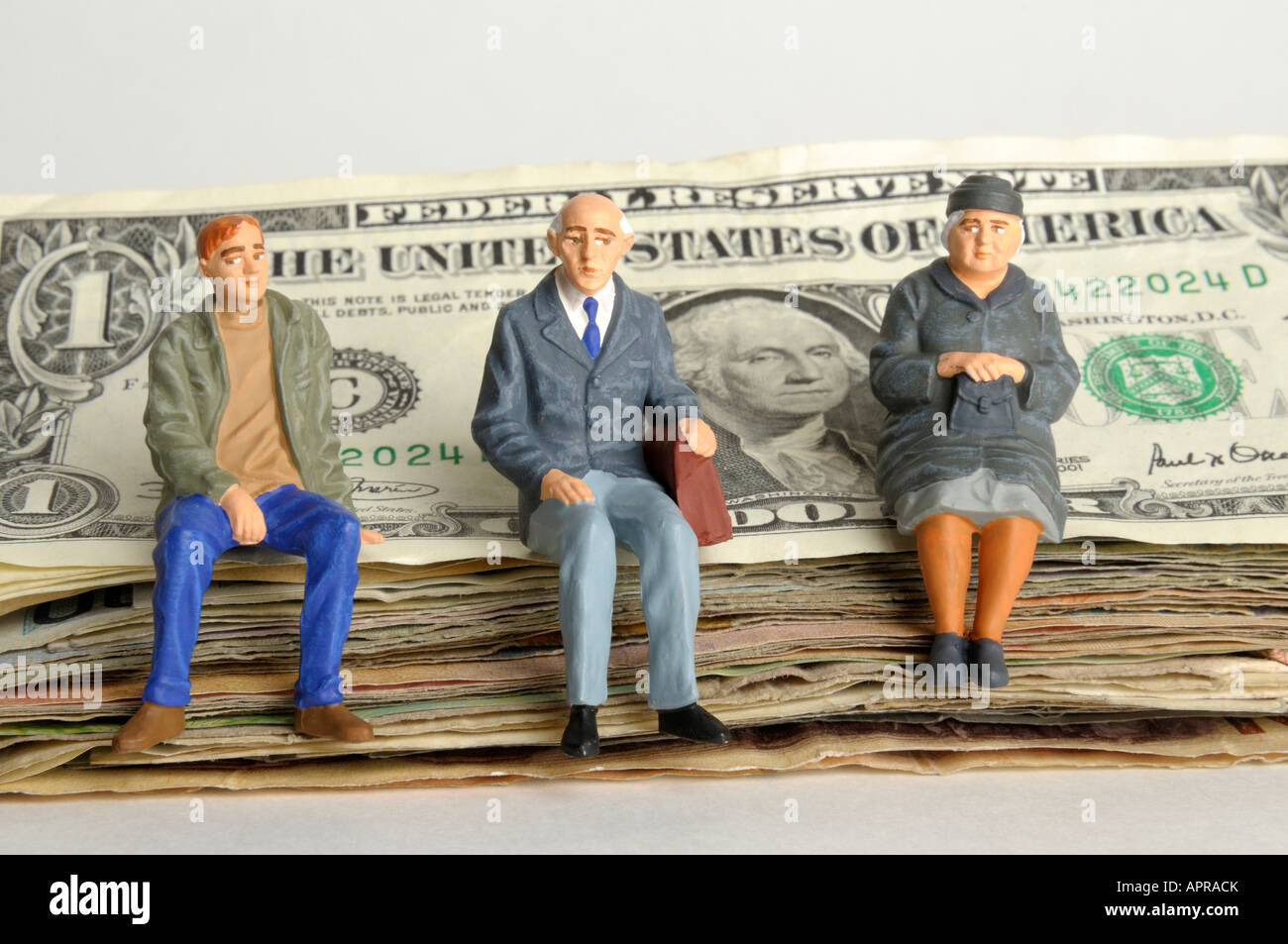 Parents / grandparents and young man figures sitting on a pile of US dollars - Savings / inheritance / pension concept - Stock Image