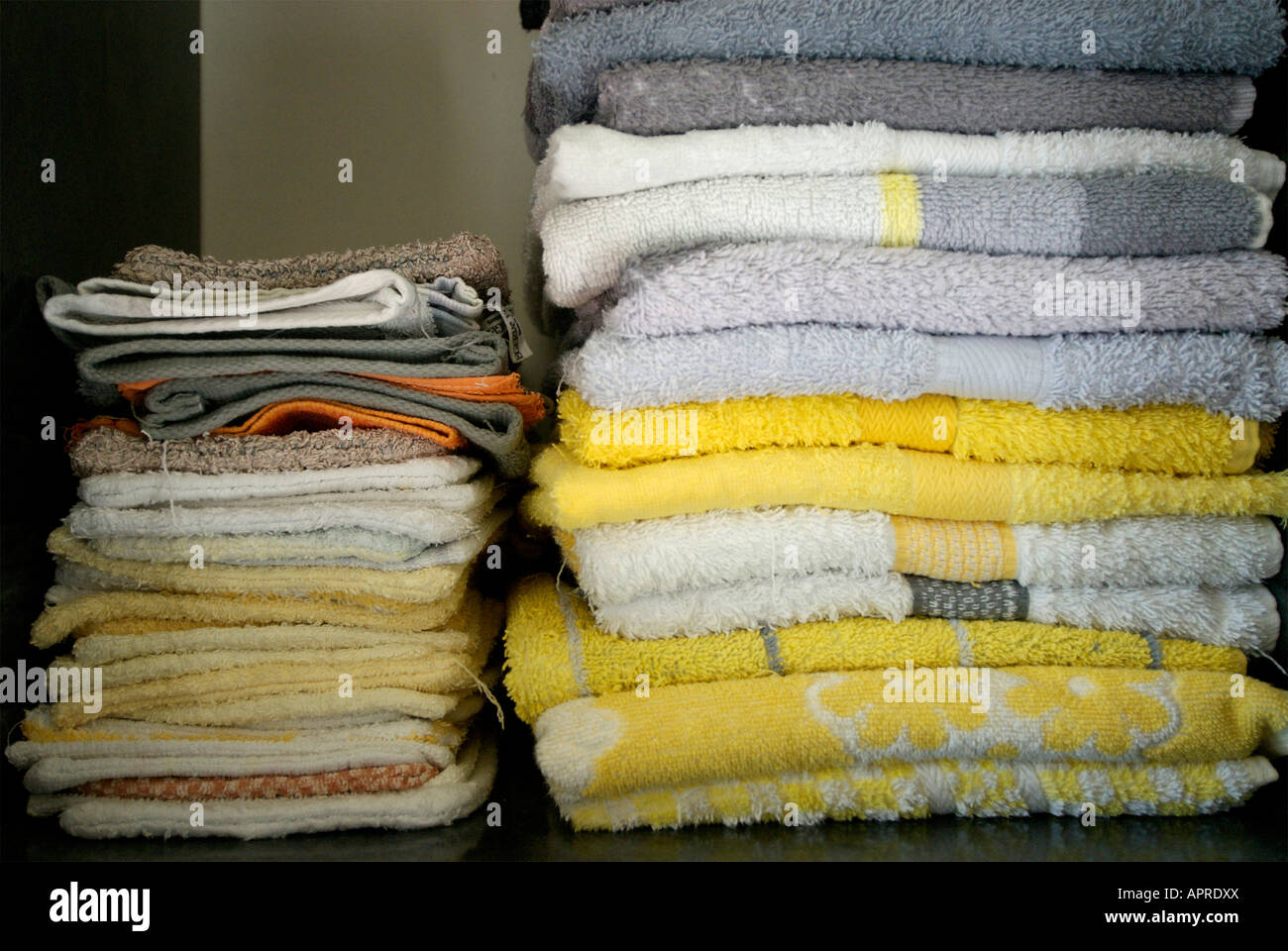 Towels and facecloths folded on a bathroom shelf - Stock Image