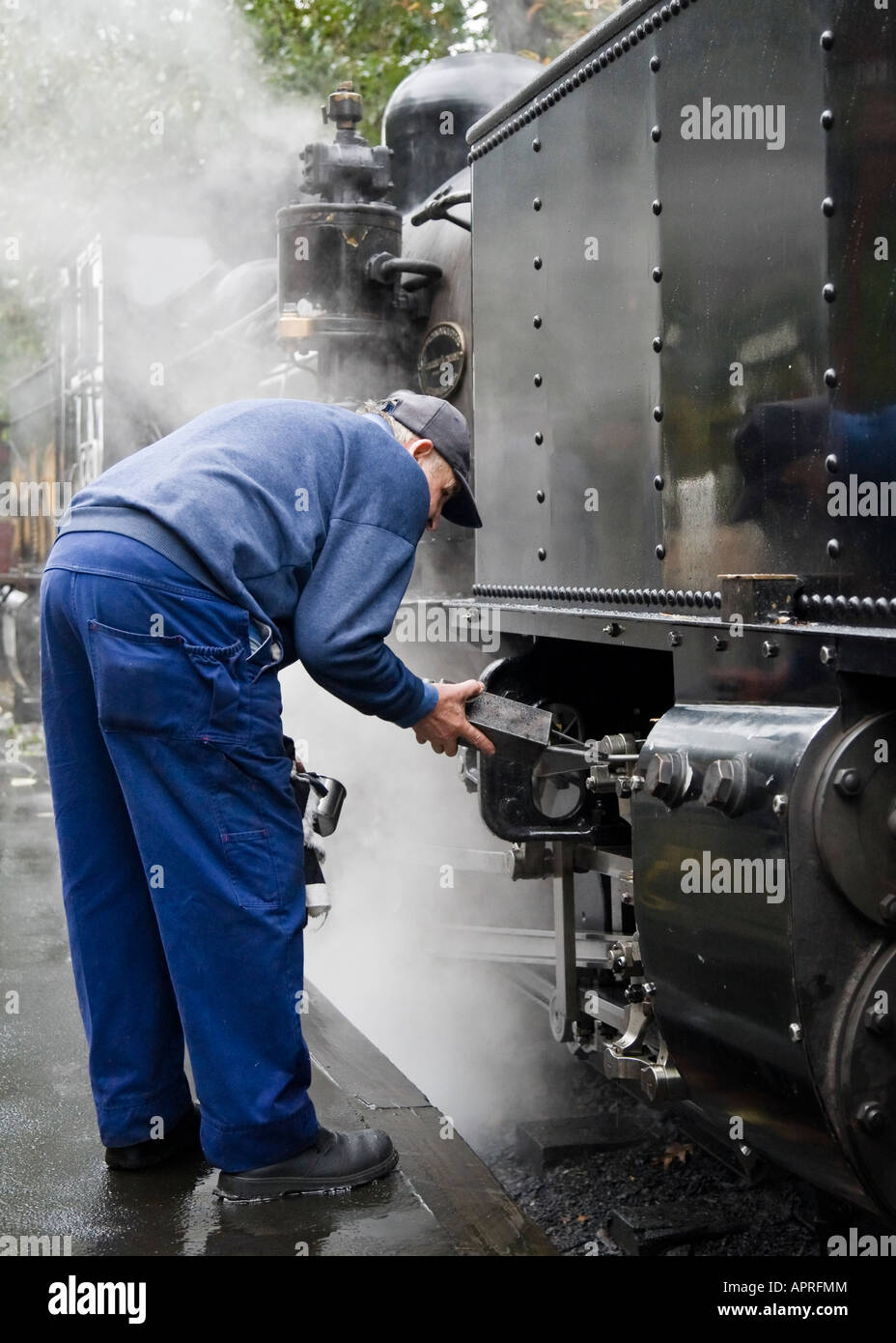 An elderly engineer in blue overalls oils the components on an old, black Victorian steam train, Melbourne, Australia - Stock Image