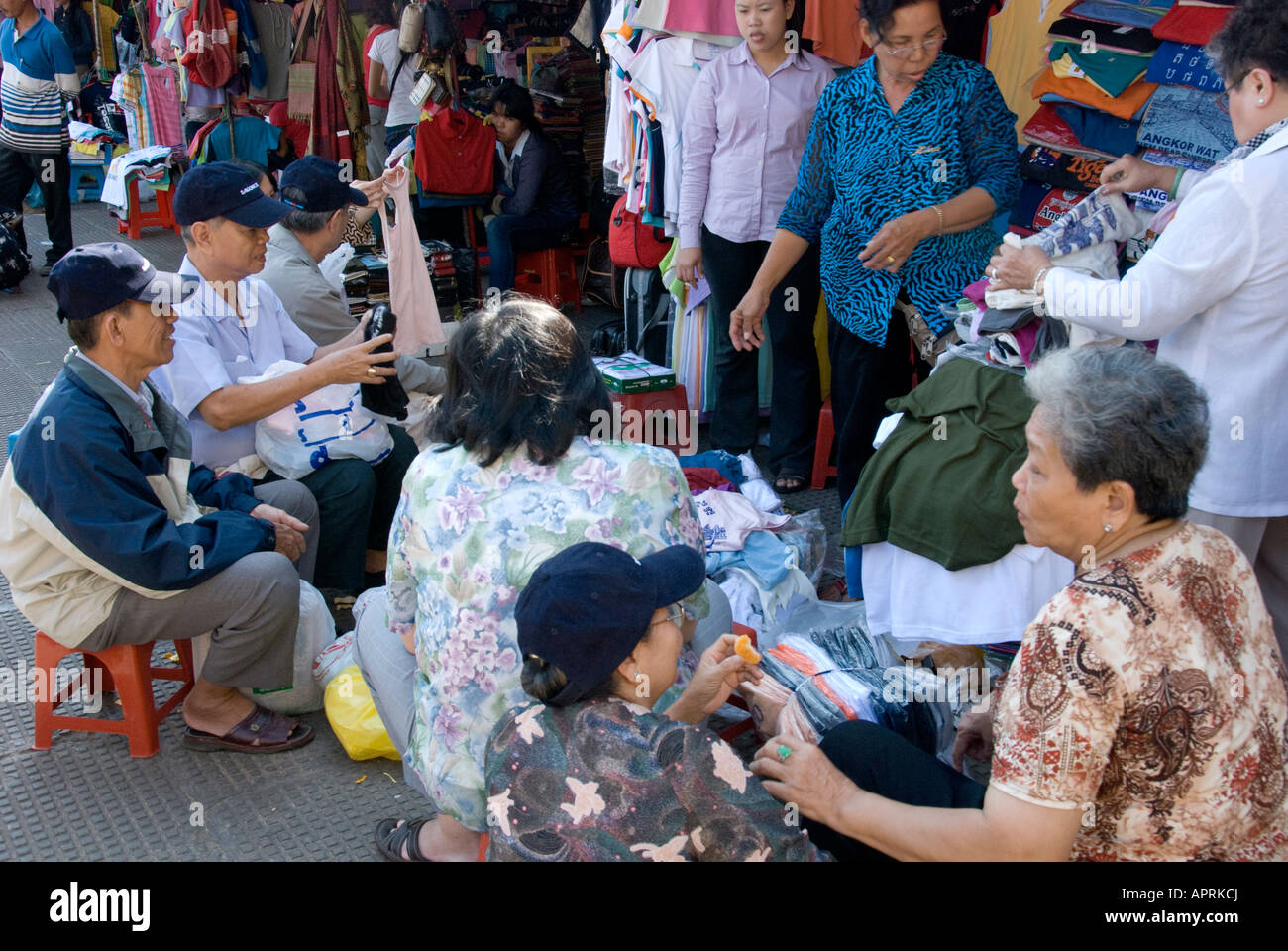 friends discussing clothes at a market stall at Psar Thmei Market (New Market or Central Market) Phnom Penh, Cambodia - Stock Image