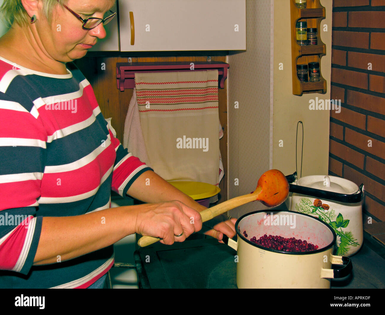 MR PR woman making jam on an old wood fired oven in an old kitchen - Stock Image