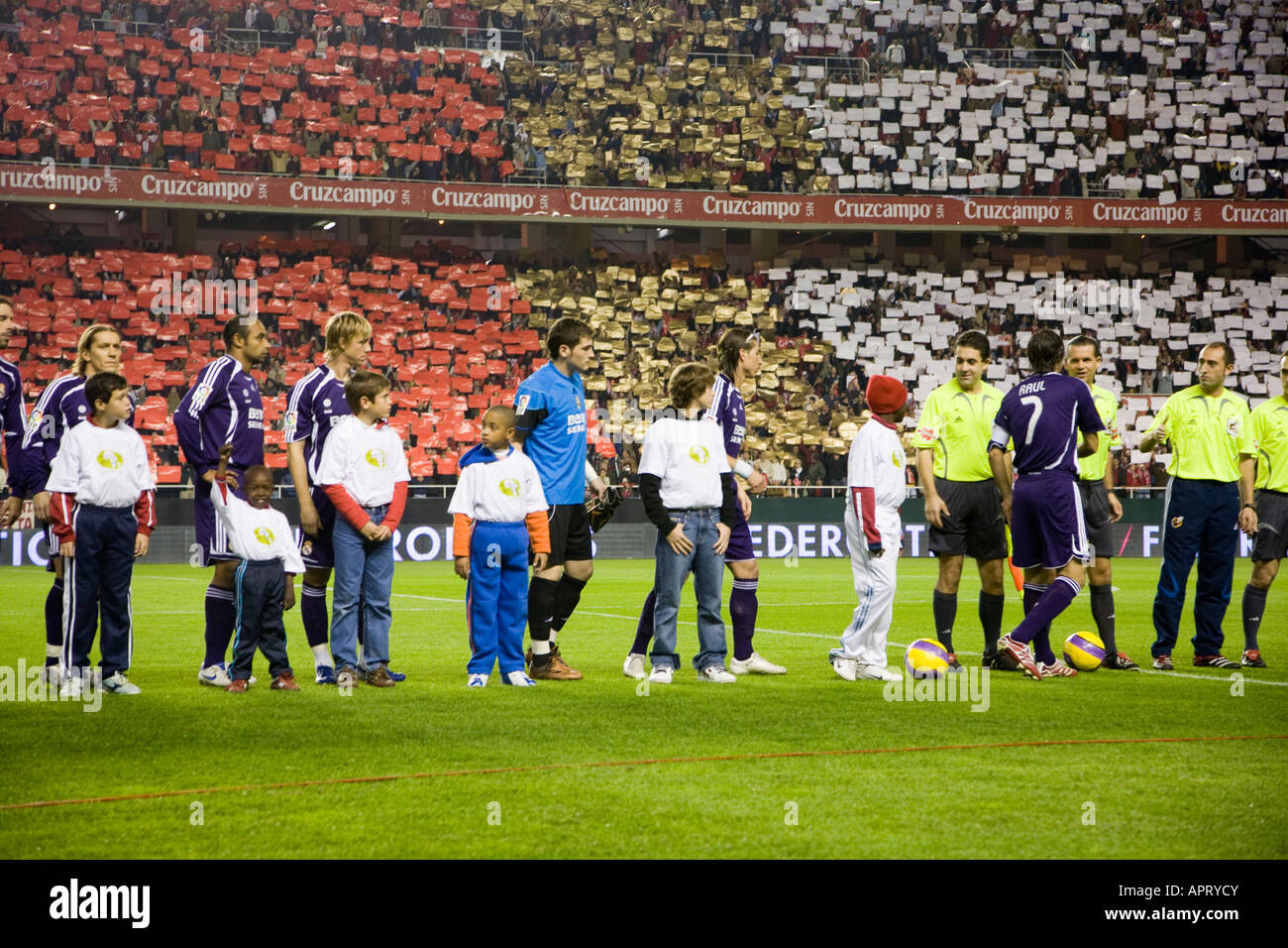 Real Madrid players forming with children before the game. - Stock Image