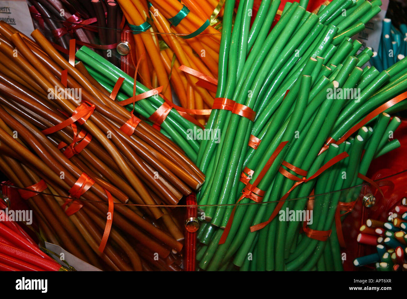 Green brown and orange sticks of Liquorice, all heaped together, tied with pieces of ribbon. candy Stock Photo