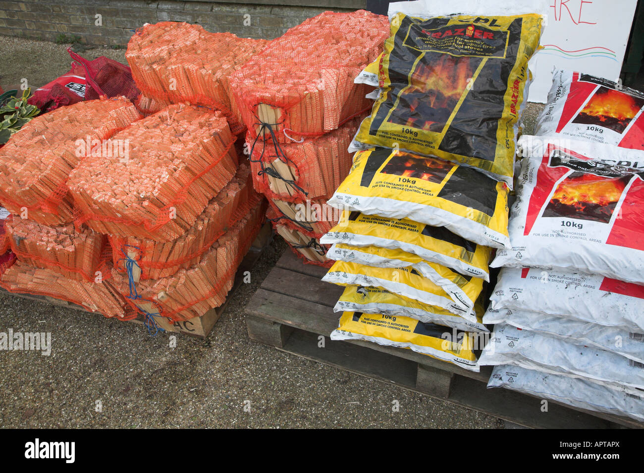 Bags of coal and fire wood on sale - Stock Image