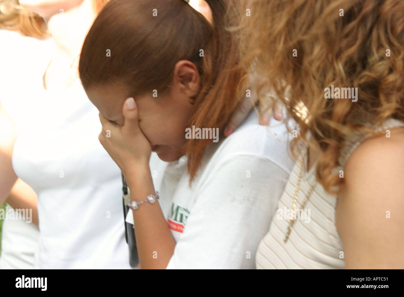 Miami Beach Florida Lummus Park Domestic Violence March audience women weeps listen to speech - Stock Image