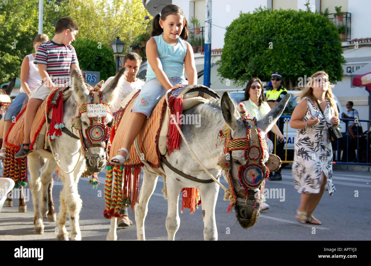 Children riding donkeys, Mijas Pueblo, Andalucia, Spain - Stock Image