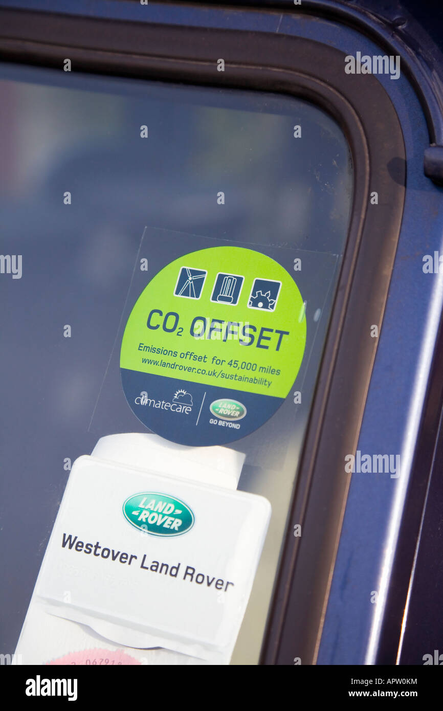 C02 Offset sticker on the windscreen of a Land Rover Defender. UK. - Stock Image