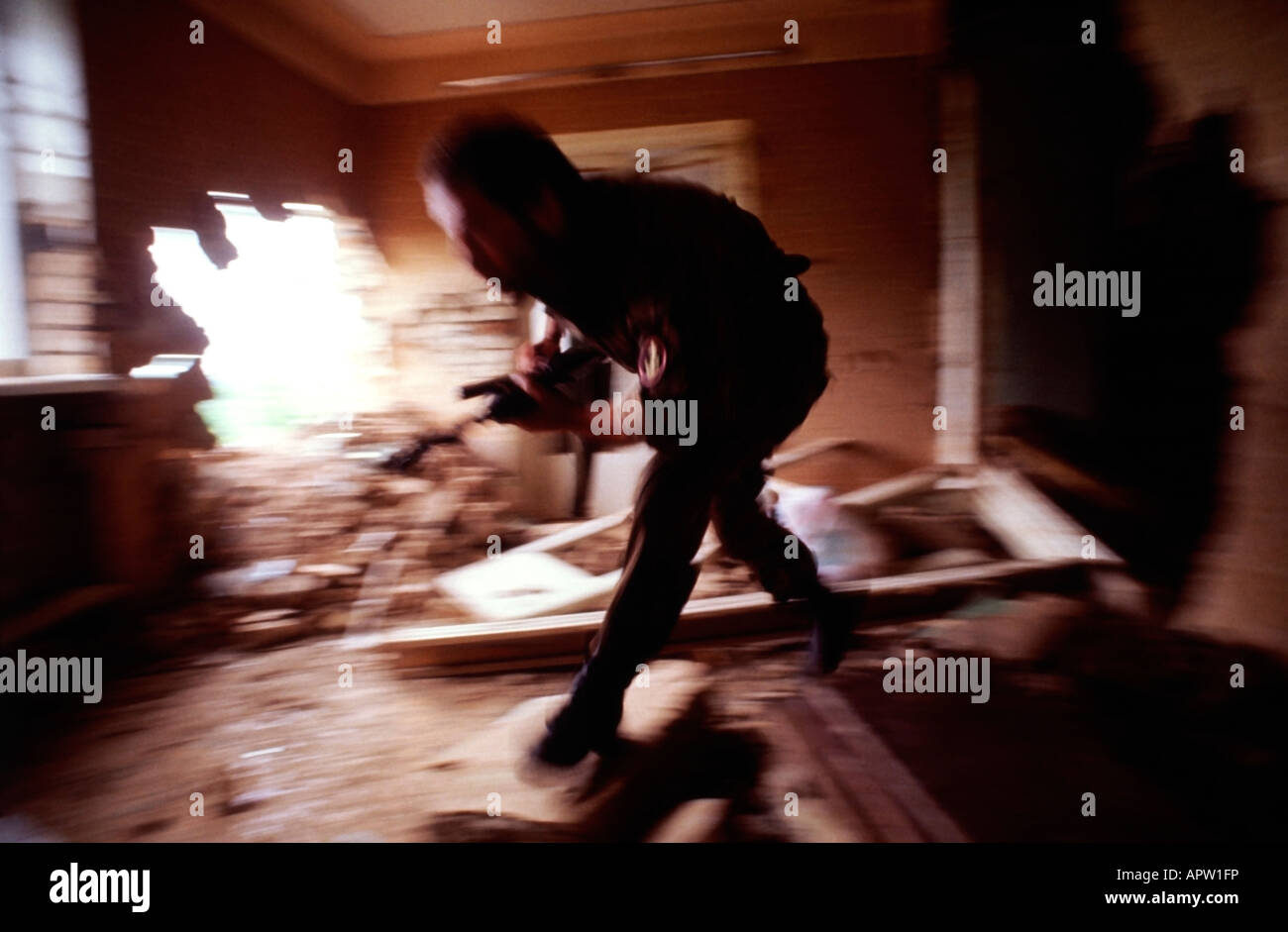 Armed soldier runs through a bombed out house during fighting in Tskhinvali the capitol of South Ossetia. - Stock Image