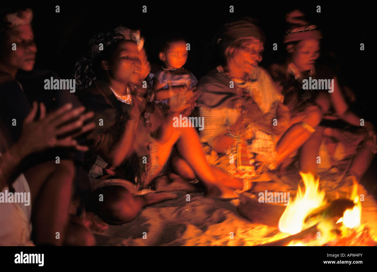 Bushwomen sitting at fire and singing Namibia Stock Photo
