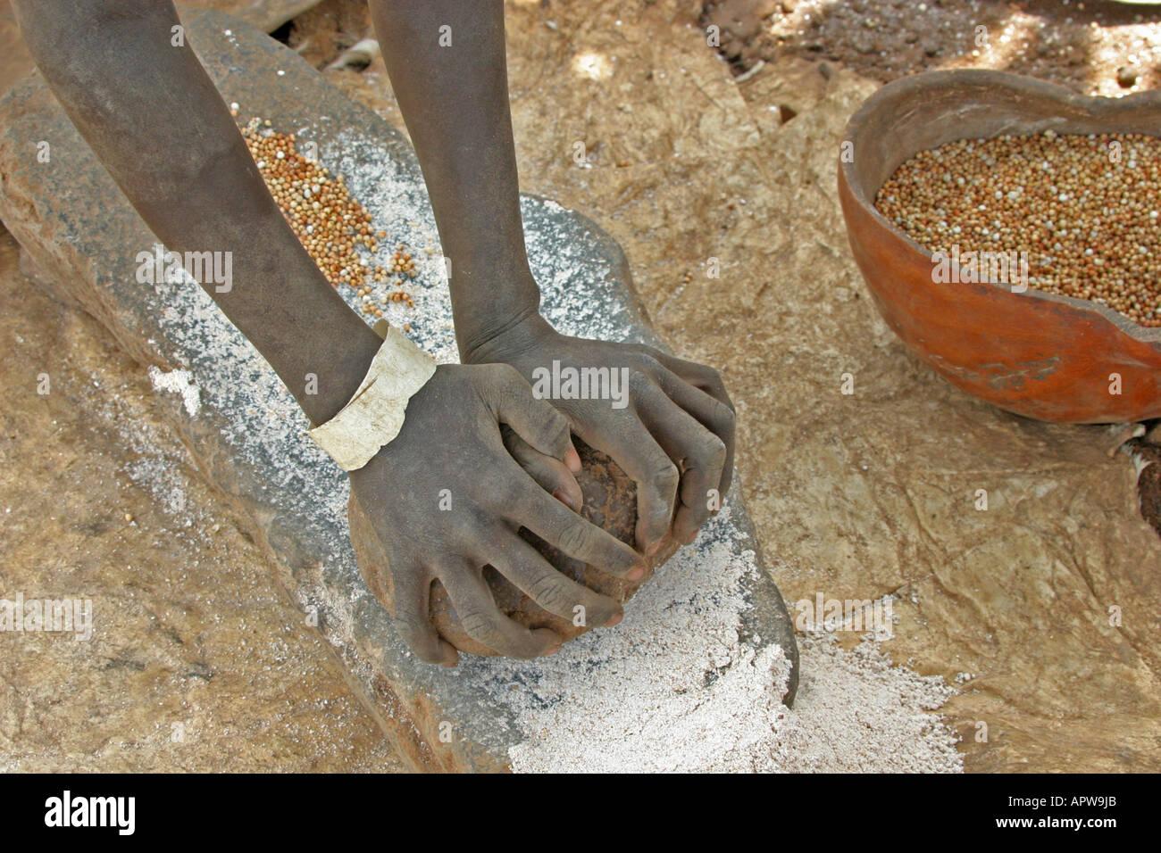 Toposa woman grinding sorghum, Sudan - Stock Image