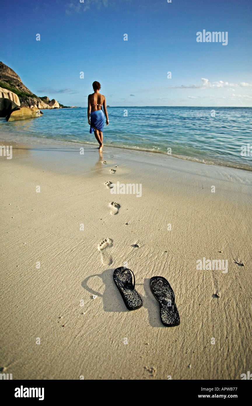 Woman walking down beach to the sea Shoes and footprints Model released Anse Source d Argent beach La Digue Island Seychelles - Stock Image