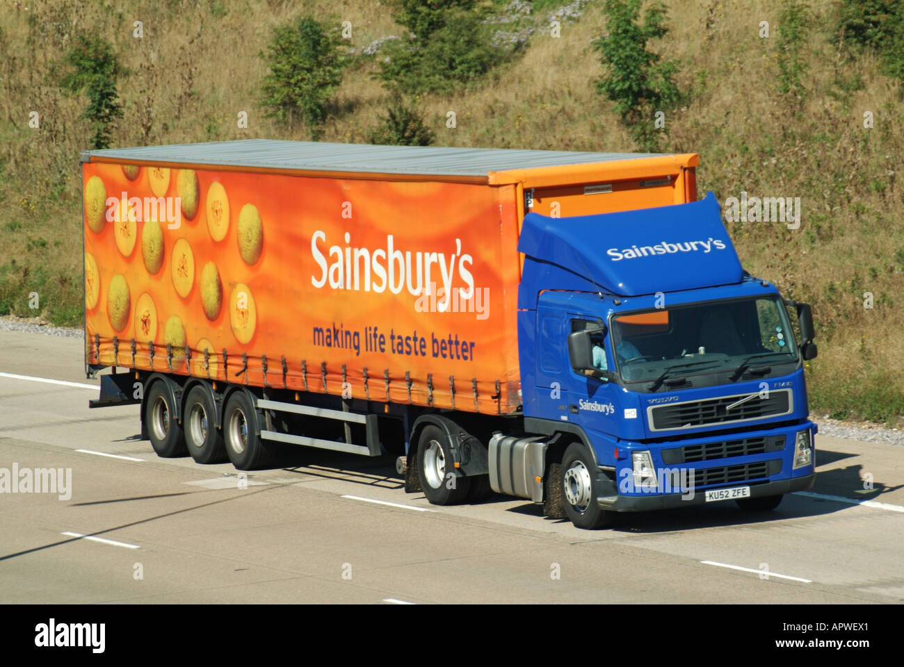 Sainsburys supermarket articulated delivery trailer and Volvo hgv truck driving along M25 motorway Stock Photo