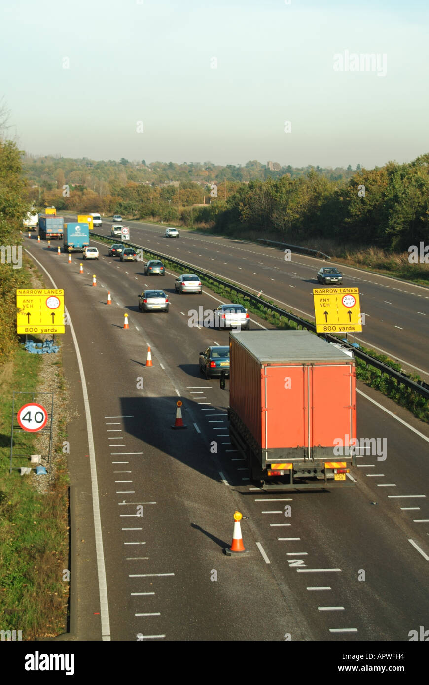 Ingatestone bypass road works approach warning signs and lane closure with speed camera road markings - Stock Image