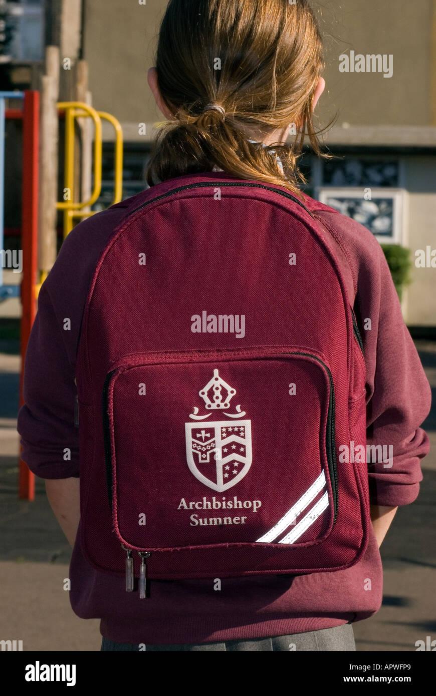 Primary schoolgirl wearing school logo backpack - Stock Image