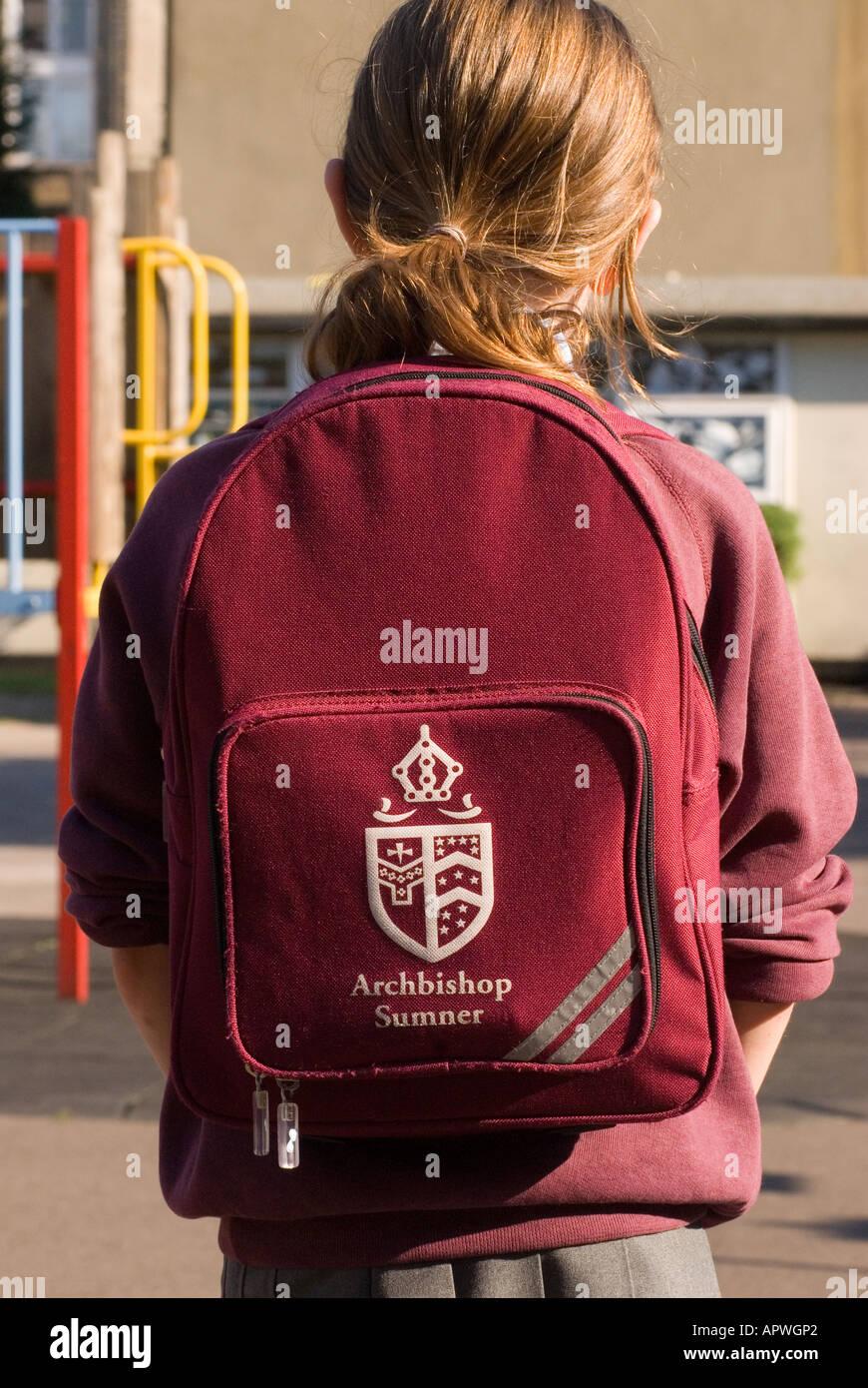 Primary schoolgirl wearing school logo backpack, London, UK. - Stock Image