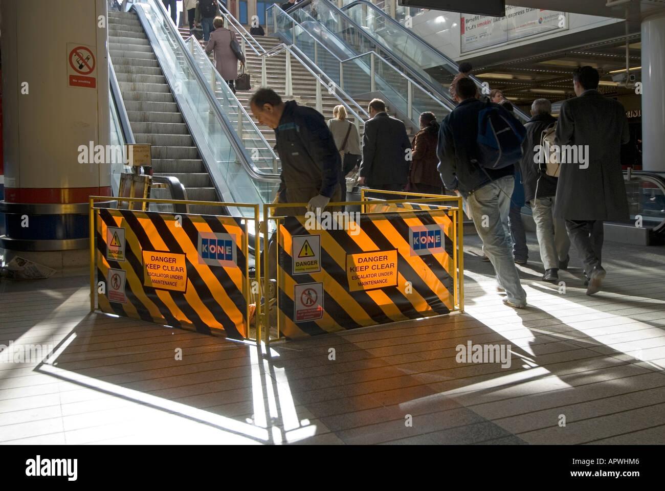 Liverpool Street mainline railway terminal concourse escalator repair crew working behind translucent barriers - Stock Image