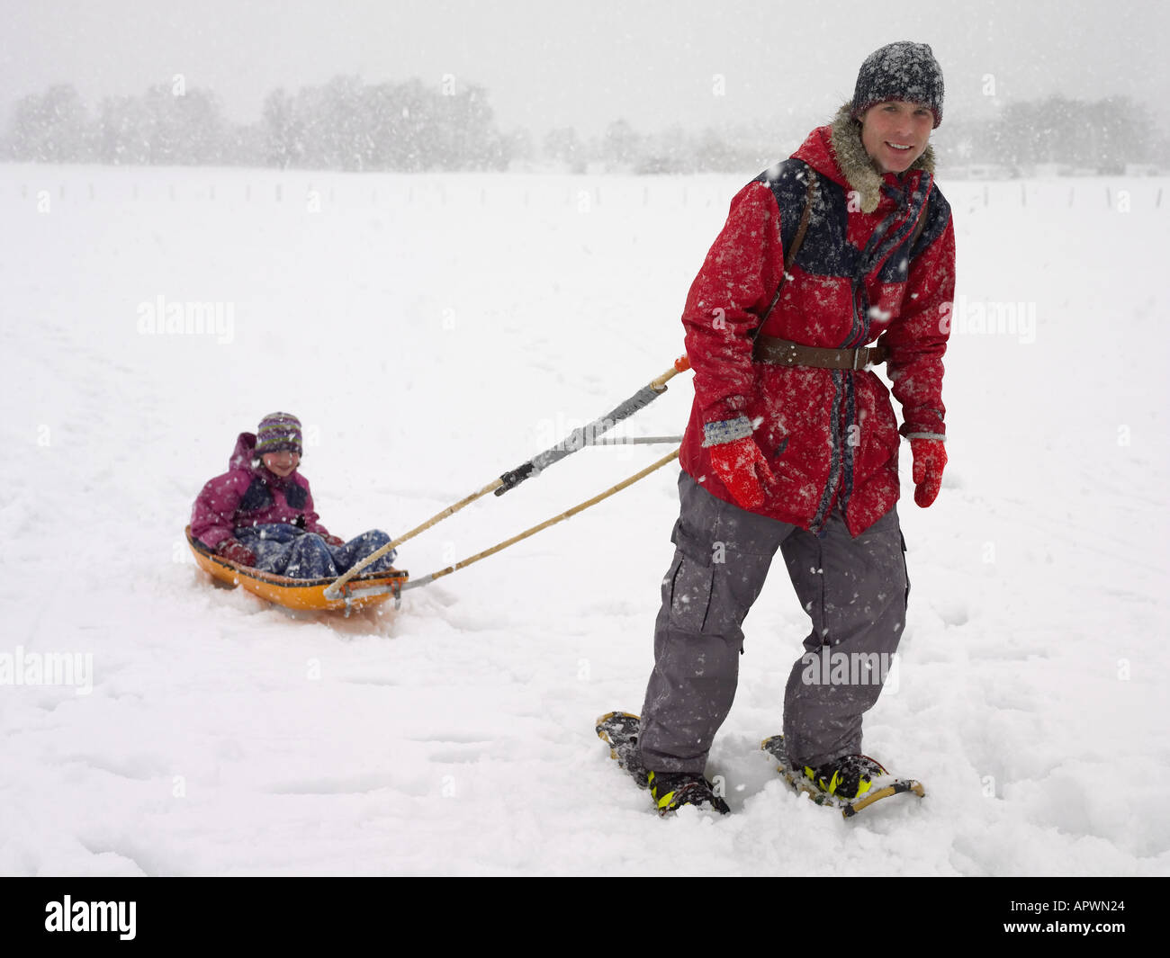 Man pulling his daughter in a sled - Stock Image