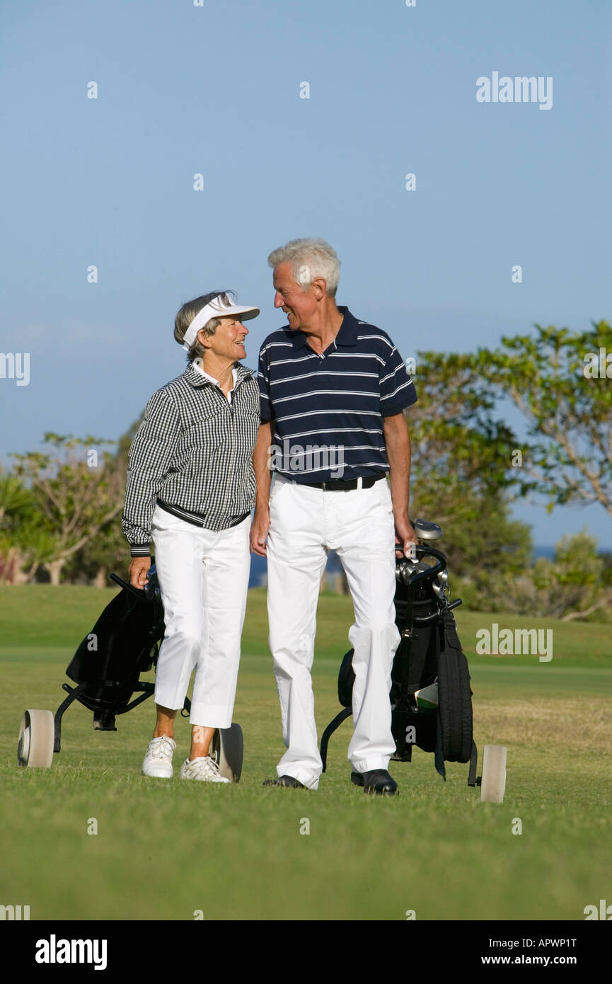 mature couple pulling golf bags over golf course - Stock Image