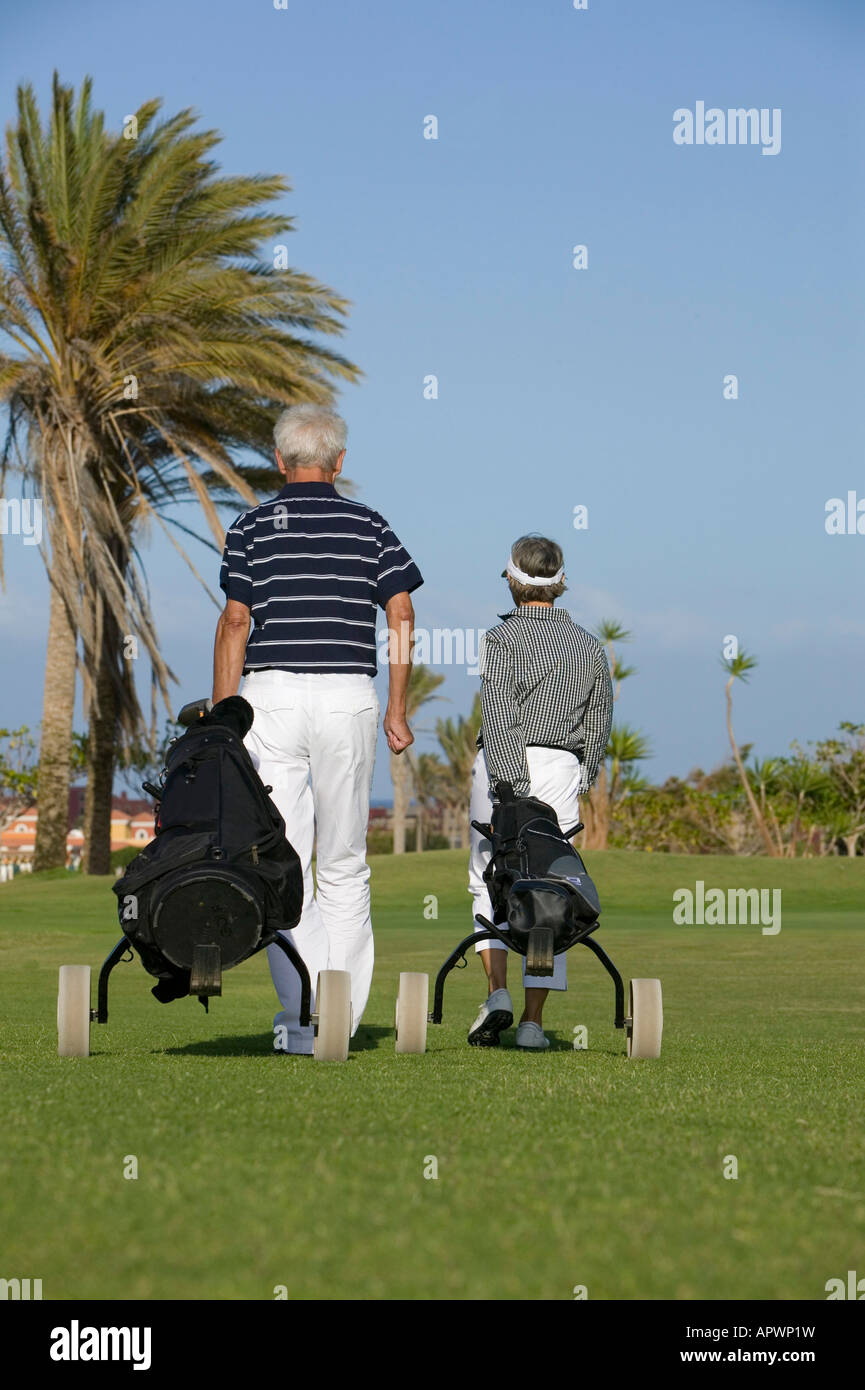 rear view of mature couple pulling golf bags over golf course - Stock Image