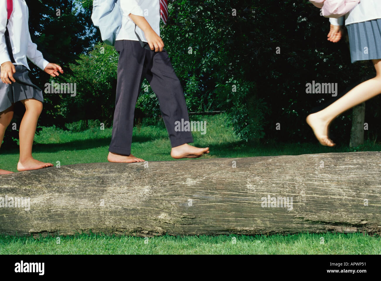 Children running along a log - Stock Image