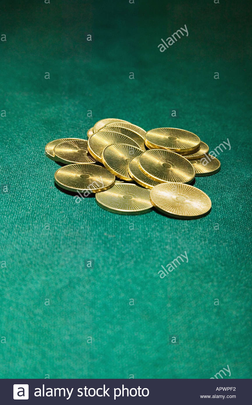 Gold coins on green surface - Stock Image