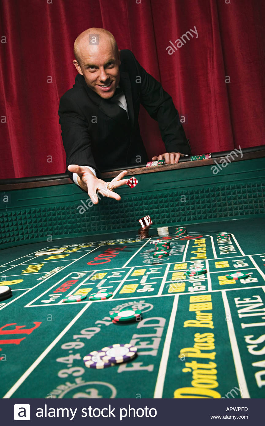 Man throwing dice at craps table - Stock Image