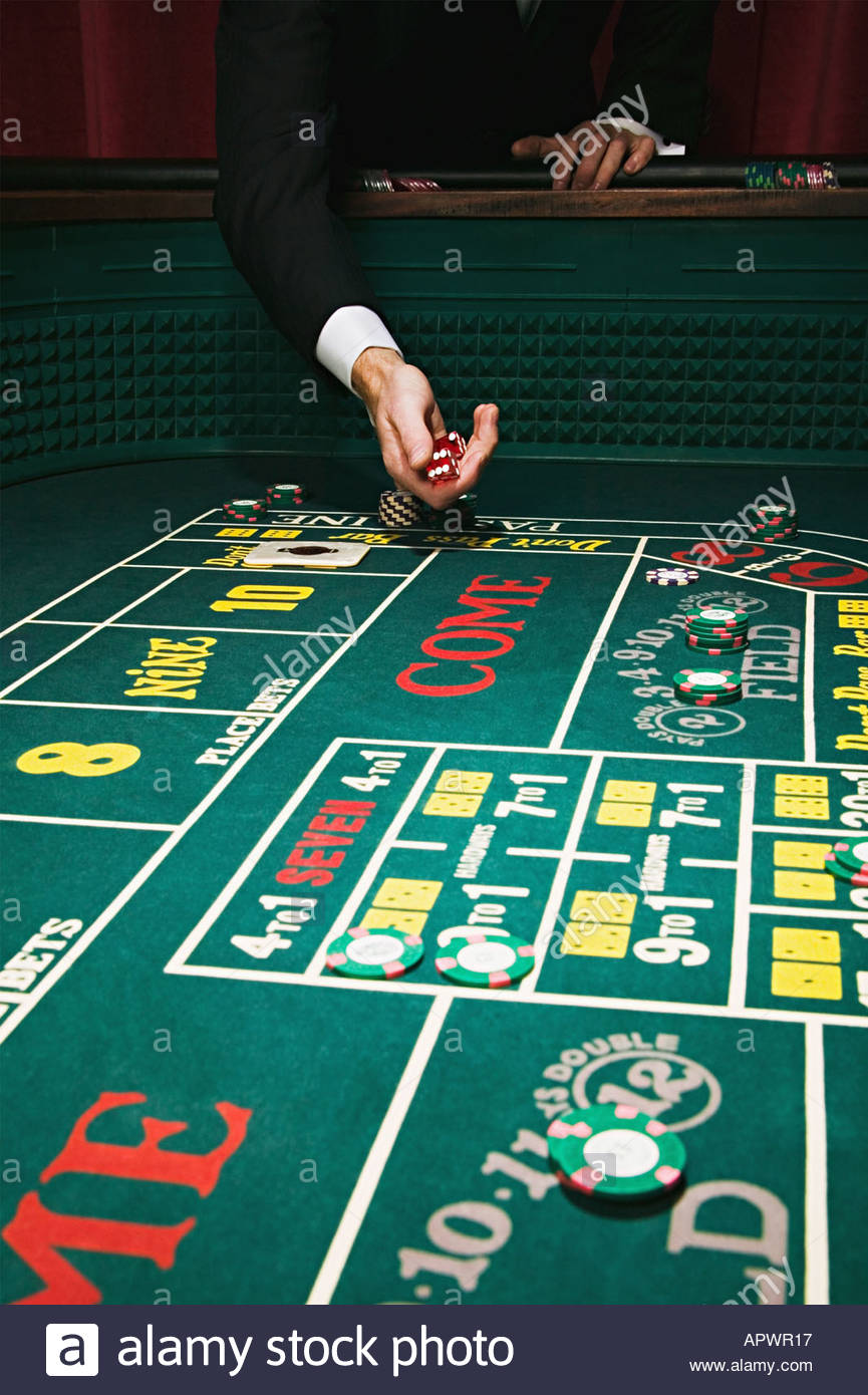 Throwing dice at a craps table - Stock Image