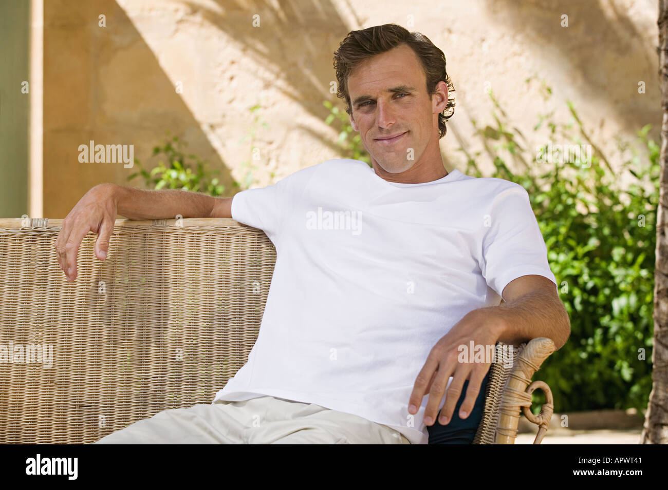 Man in a wicker chair - Stock Image