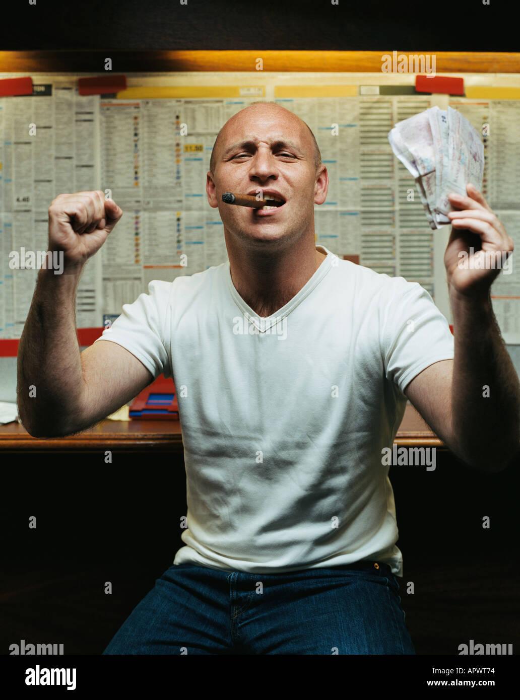 Man celebrating win at betting shop - Stock Image