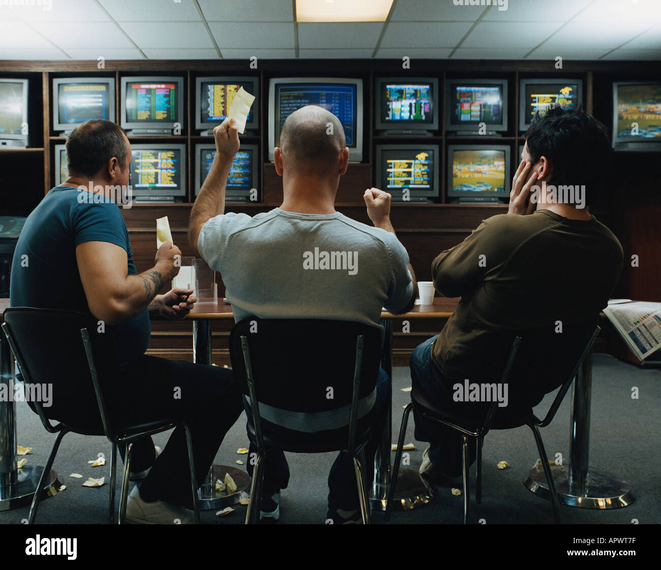 Three men in a betting shop Stock Photo