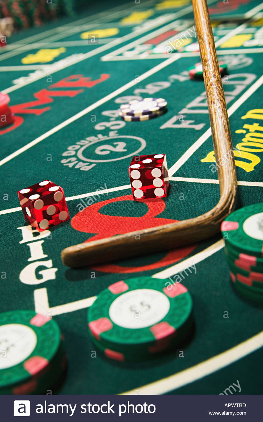 Croupier stick clearing craps table - Stock Image