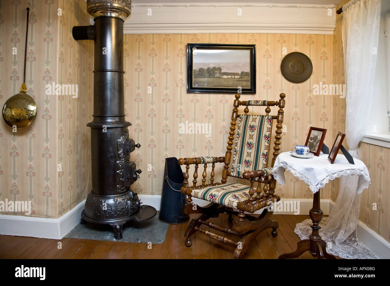 Old rocking chair at the woodburning stove - Stock Image