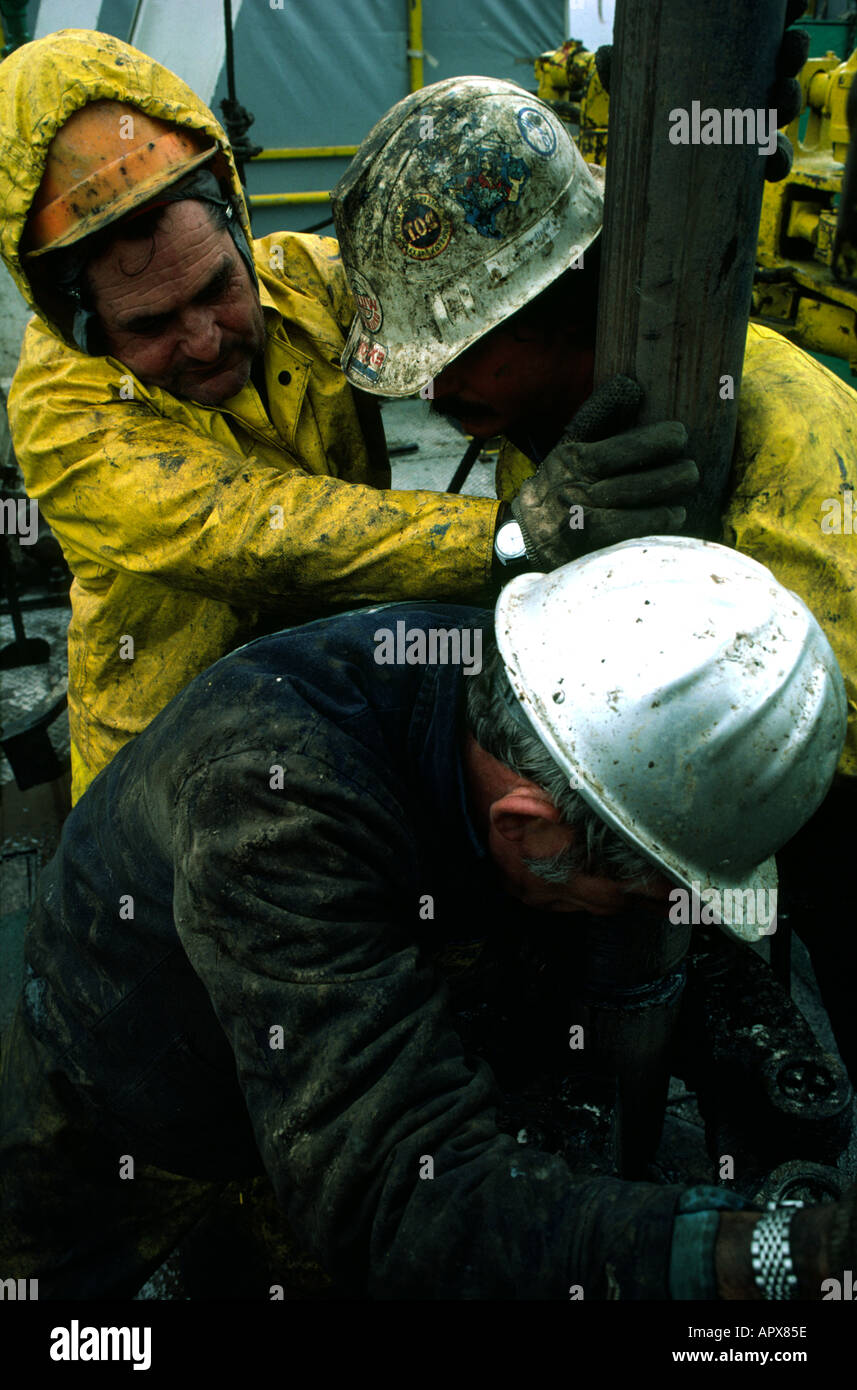 roughnecks changing a drill bit on the floor of an oil rig - Stock Image