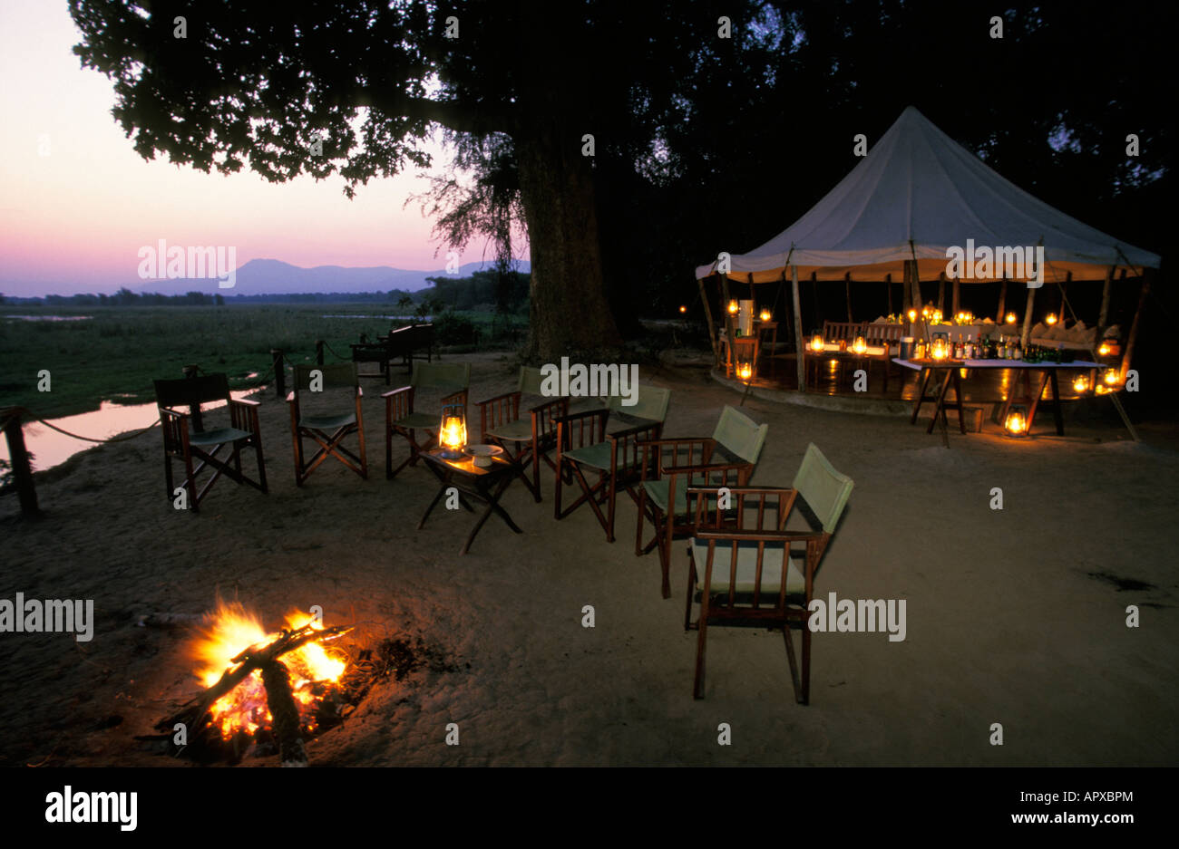 Chairs Set Around A Campfire And A Boma Lit With Oil Lamps In The  Background At Sausage Tree Camp Zambia