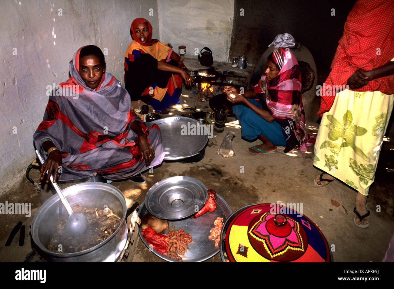Three women share the cooking in a Nubian kitchen while a fourth woman watches from the side - Stock Image