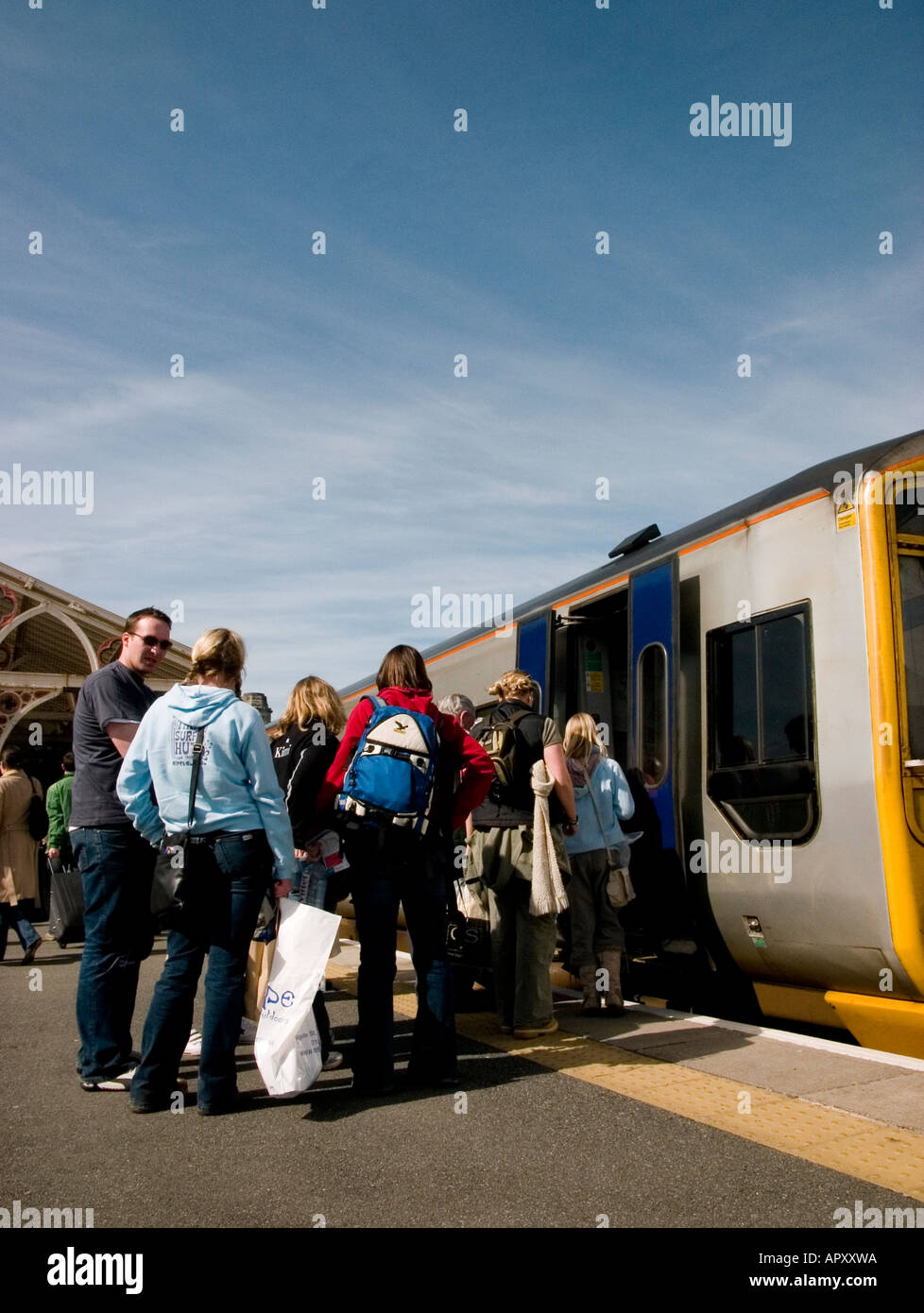 Passengers boarding a train at Aberystwyth railway station, wales UK - Stock Image