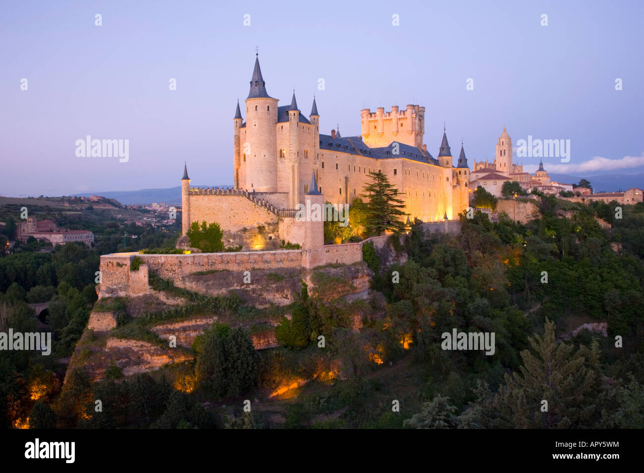 Segovia, Castile and León, Spain. The Alcázar illuminated at dusk, the cathedral visible beyond. - Stock Image