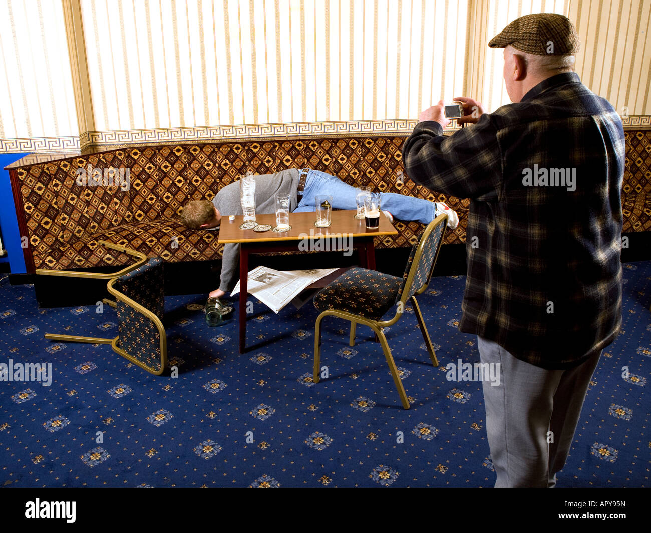 Old Man With Flat Cap Taking A Picture Of Drunk Young Man Using A