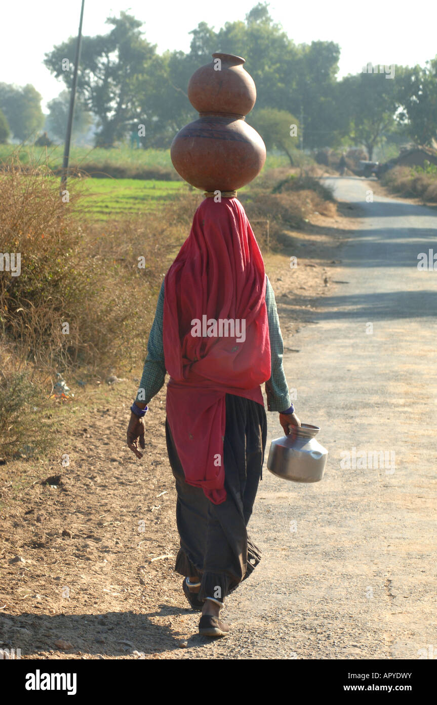 woman with waterjug at her head in india - Stock Image