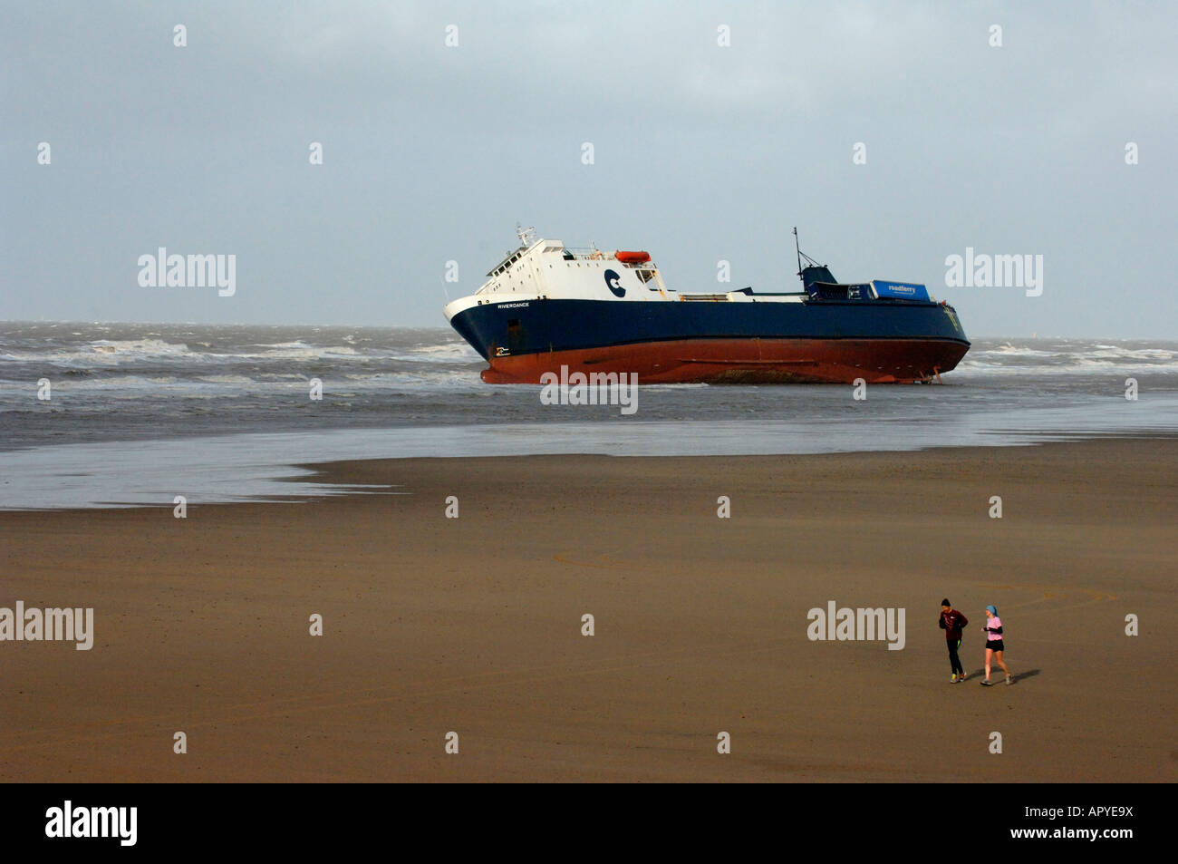 A couple jogging on the beach at Cleveleys pass the stricken Ro-Ro Ferry 'Riverdance' - Stock Image