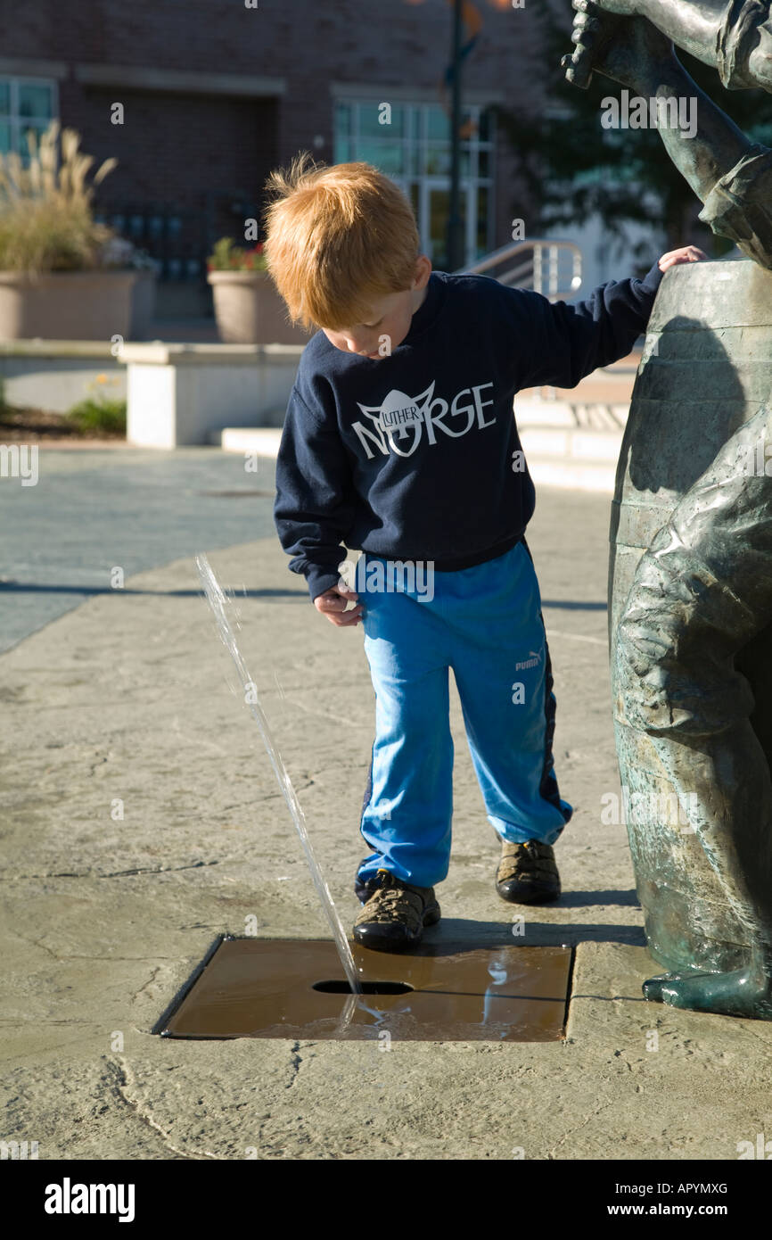 ILLINOIS Moline Young boy standing next to spout of water from fountain sculpture in downtown area - Stock Image