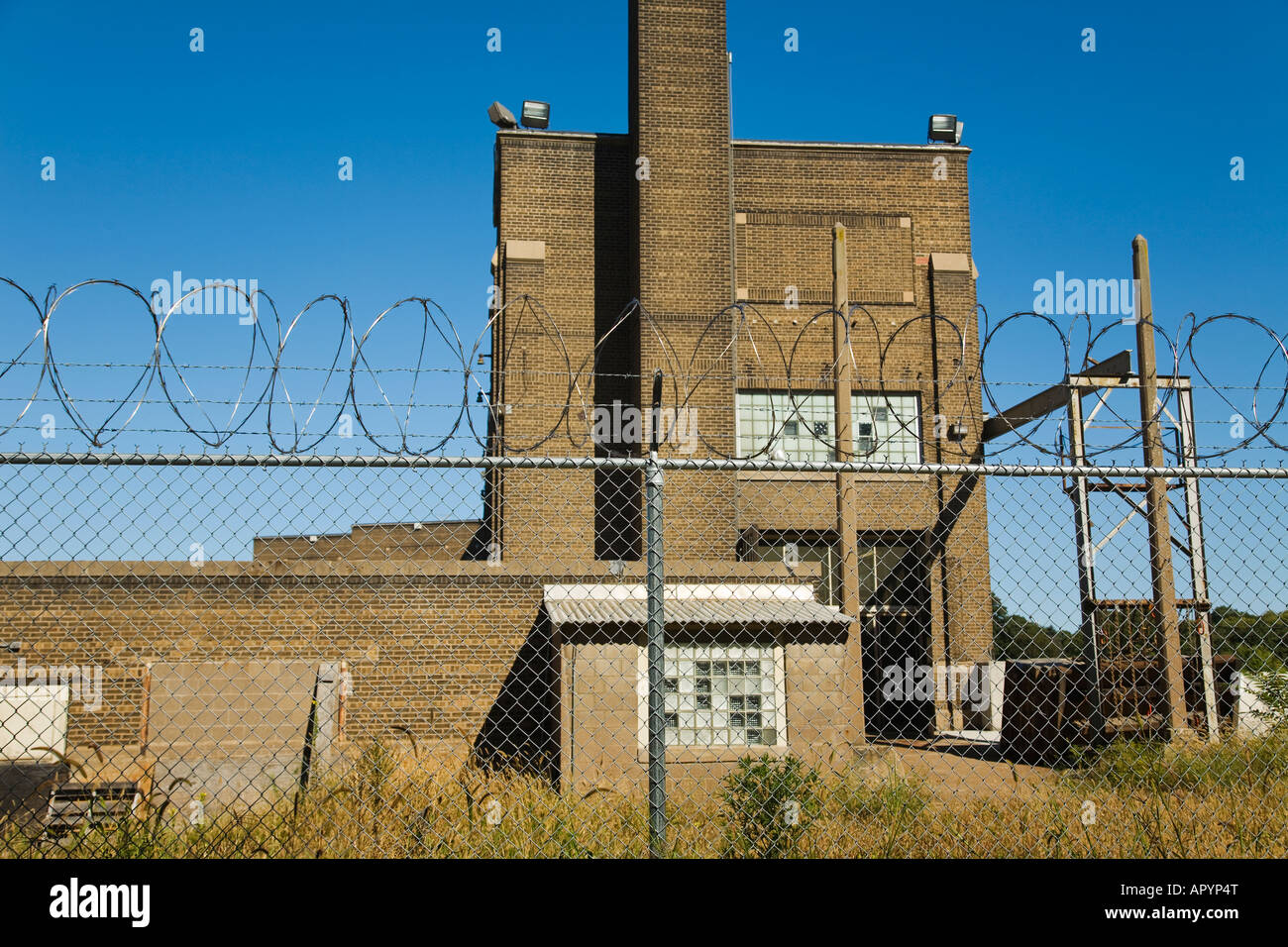 ILLINOIS Moline Coils of barbed wire above metal chain link fence Sylvan Island Park old brick building former factory - Stock Image