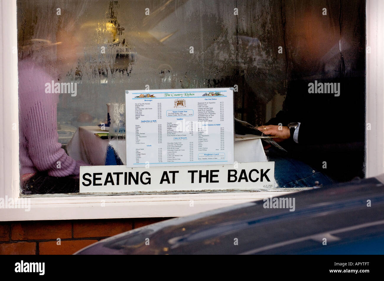 Condensation obscures the view of a couple sat at a table in the window of a cafe. Picture by Jim Holden. - Stock Image