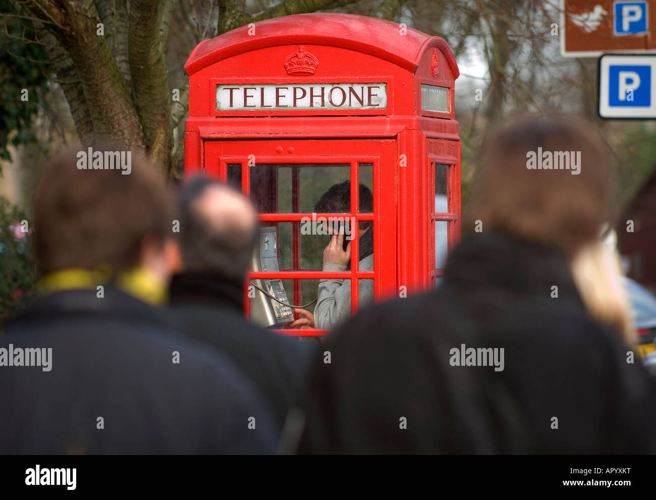 A young man using a red telephone box in a busy urban street. Picture by Jim Holden. Stock Photo
