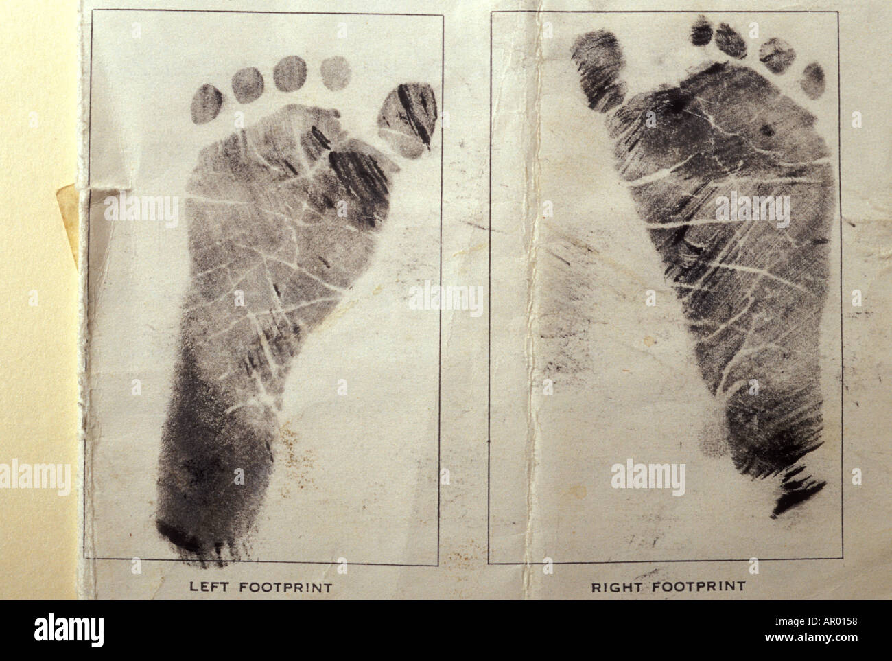 Baby s footprints from ink on birth certificate - Stock Image